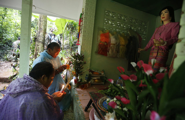 Relatives of 12 young soccer team members and their coach pray at a shrine for their rescue after going missing in a large cave, Wednesday, June 27, 2018, in Mae Sai, Chiang Rai province, northern Thailand. Rain is continuing to fall and water levels keep rising inside a cave in northern Thailand, frustrating the search for the boys and their soccer coach who have been missing since Saturday. (Photo by Sakchai Lalit/AP Photo)