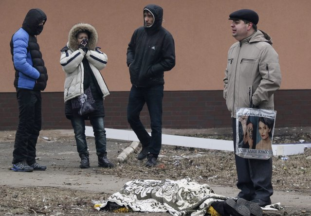 Local residents react as they stand near the covered body of man, who was killed during shelling in the eastern Ukrainian city of Mariupol, 24 January 2015. (Photo by Sergey Vaganov/EPA)