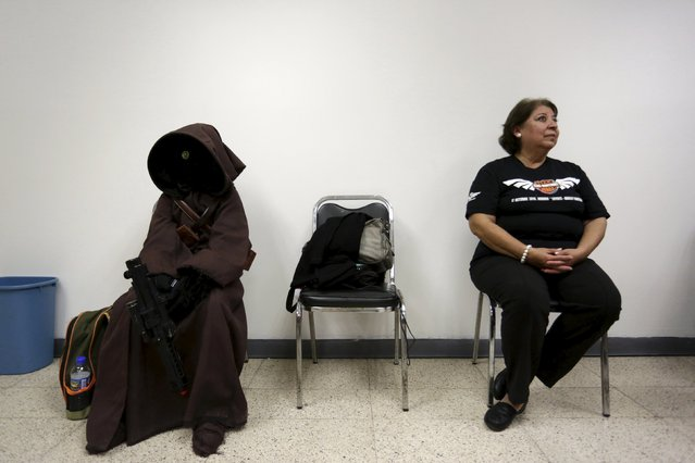 A woman sits next to a cosplayer dressed as a character from the Star Wars movie series during an event organised by Star Wars fan club Monterrey in Monterrey, Mexico, December 13, 2015. (Photo by Daniel Becerril/Reuters)