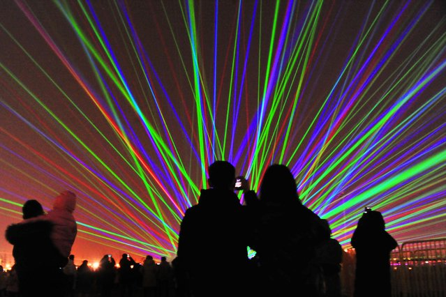 People take photos of a laser show at Dishui Lake area on January 2, 2021 in Shanghai, China. (Photo by Yang Jianzheng/VCG via Getty Images)