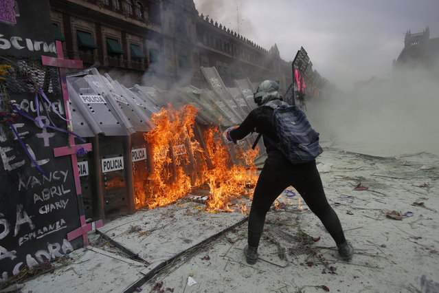 A demonstrator throws burning gasoline at a police shield wall that is closing a breach on a barricade protecting the National Palace during a march to commemorate International Women's Day and protest against gender violence, in Mexico City, Monday, March 8, 2021. (Photo by Ginnette Riquelme/AP Photo)