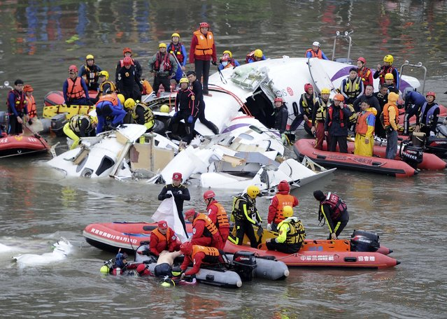 Emergency personnel retrieve the body of a passenger from the wreckage of a TransAsia Airways turboprop ATR 72-600 aircraft after it was crashed in a river, in New Taipei City, February 4, 2015. (Photo by Reuters/Stringer)