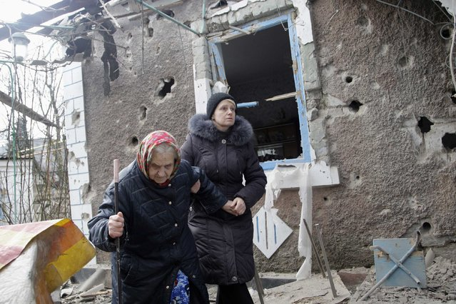 People walk outside a house, which according to locals was recently damaged by shelling, in Donetsk February 3, 2015. (Photo by Alexander Ermochenko/Reuters)