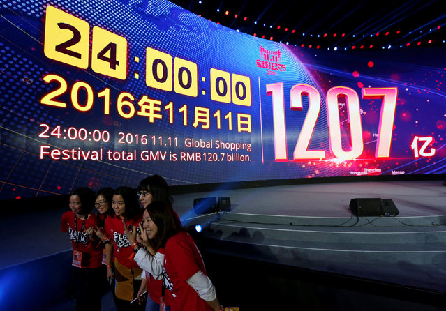 Attendants celebrate in front of a screen displaying the total value of goods sold during Alibaba Group's 11.11 Singles' Day global shopping festival in Shenzhen, China, November 12, 2016. (Photo by Bobby Yip/Reuters)