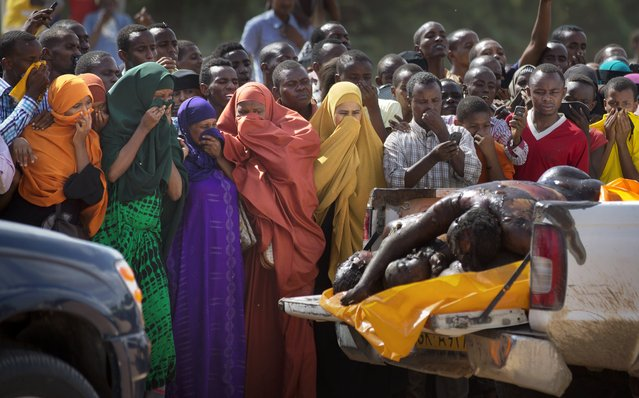 Women in the crowd cover their faces to protect against the smell as authorities display the bodies of the alleged attackers before about 2,000 people in a large open area in central Garissa, Kenya Saturday, April 4, 2015. (Photo by Ben Curtis/AP Photo)