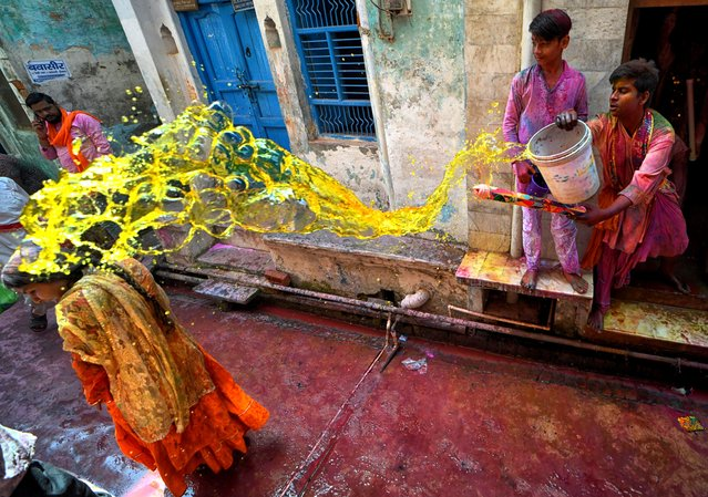 A man powering colour onto a woman during the Lathmar Holi Festival of Barsana in Mathura on March 23, 2021. The myth behind this festival is related to Hindu God Lord Krishna who as per local belief came from his hometown Nandgaon to Barsana to tease Radha (a Hindu goddess and a consort of the god Krishna) and her friends. For more than 100 years, women of Barsana still maintaining the ritual. (Photo by Avishek Das/SOPA Images/Rex Features/Shutterstock)