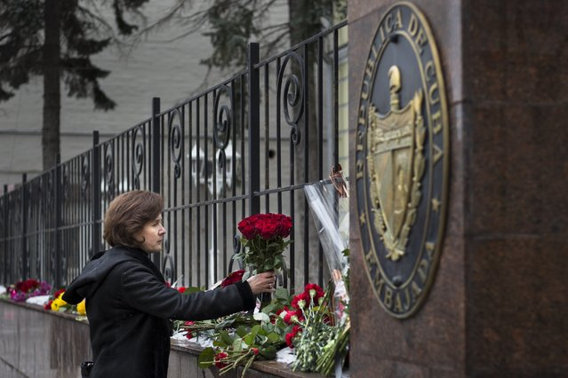A woman lays a bunch of flowers to pay her last respect to Cuban President Fidel Castro, who has died on Friday, November 25, 2016 at age 90 at the Cuban Embassy in Moscow, Russia, Saturday, November 26, 2016. Russian President Vladimir Putin said in a condolences telegram to Raul Castro, that Fidel Castro was a sincere and reliable friend of Russia. (Photo by Alexander Zemlianichenko/AP Photo)