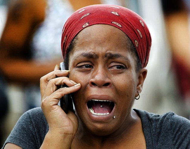 Nicole Webb cries while waiting for her 9-year-old son, a student at Ronald E. McNair Discovery Learning Academy in Decatur, Georgia, on August 20, 2013. A suspect was in custody after reports of gunfire at the elementary school. Superintendent Michael Thurmond said all students at the school were accounted for and safe and that he is not aware of any injuries. (Photo by John Bazemore/Associated Press)