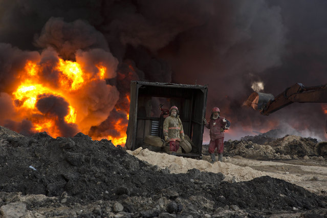 Fire fighters work to well an oil fire set by Islamic State militants in Qayara, south of Mosul, Iraq, Monday, November 28, 2016. (Photo by Maya Alleruzzo/AP Photo)
