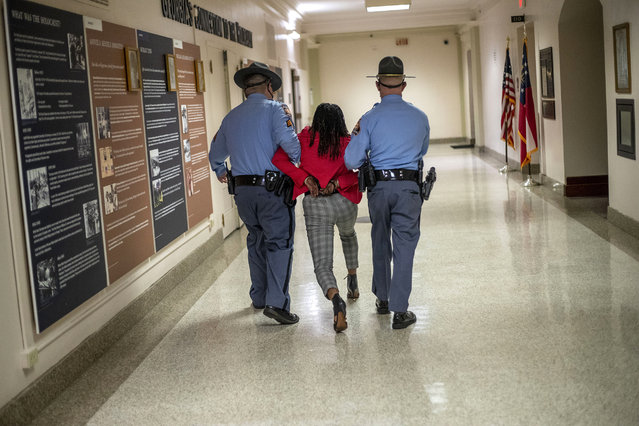"Rep. Park Cannon (D-Atlanta) is escorted out of the Georgia Capitol by Georgia state troopers after being asked to stop knocking on a door that lead to Gov. Brian Kemp's office while Kemp was speaking after signing a sweeping overhaul of state elections behind closed doors in Atlanta, Thursday, March 25, 2021. An attorney for Cannon says it's ""law enforcement overreach"" to charge the Georgia House member with two felonies. (Photo by Alyssa Pointer/Atlanta Journal-Constitution via AP Photo)"
