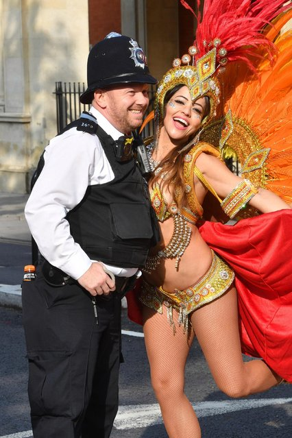 A grinning police officer poses with a dancer during the Notting Hill Carnival in London, Britain on August 27, 2018. (Photo by Yui Mok/PA Images via Getty Images)