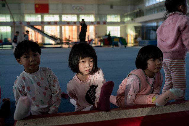 In this picture taken on January 11, 2021, young gymnasts stretch their legs at the Li Xiaoshuang Gymnastics School in Xiantao, Hubei province. This summer's delayed Tokyo Olympics, which are now due to start on July 23, 2021, will be the defining moment for Chinese gymnasts who have trained relentlessly since as young as age four in the pursuit of gold. (Photo by Nicolas Asfouri/AFP Photo)