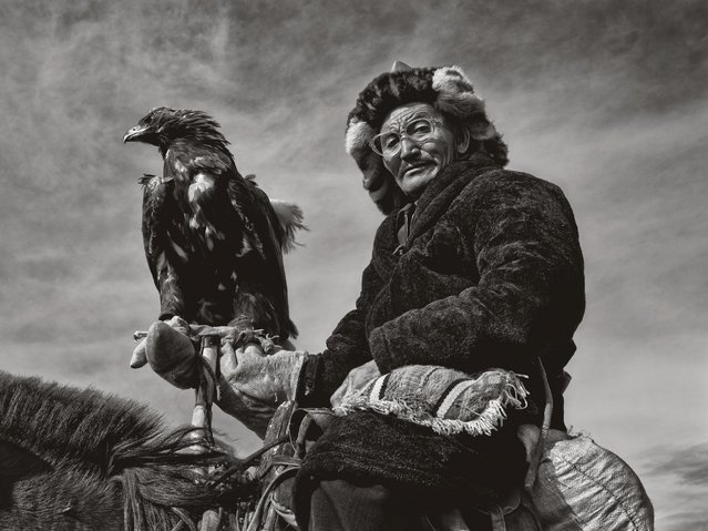 A Kazakh hunter sits on top of his horse with his eagle. (Photo by Palani Mohan)