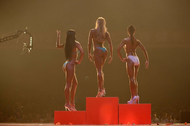"""""""""""Bikini fitness"""" competitors stand on the podium during a bodybuilding contest in Zhengzhou, Henan province, September 16th, 2013. More than 20 professionals – including a dozen from China – were competing in the Bodybuilding Grand Prix in the central Chinese city for a top prize worth 80,000 yuan (13,000 USD). They were joined by scores of amateurs from across the country, in what event organisers said was a sign of the increasing popularity of muscle building in China. Bodybuilding has at least a century of history in China, but fell out of favor following the Communist revolution in 1949, when competitions were sometimes banned and the sport condemned as western and bourgeois. But it has since enjoyed a resurgence and competitors say the growing number of competitions are boosting the ranks of local professionals. (Photo by Ed Jones/AFP Photo)"""