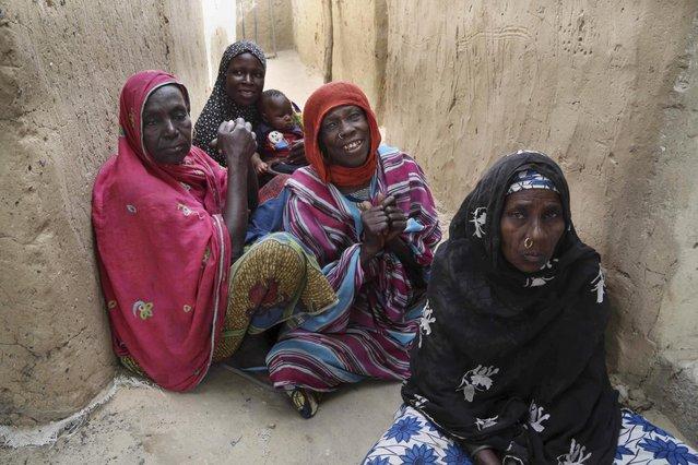 Women sit on the ground in the recently retaken town of Damasak, Nigeria, March 20, 2015. (Photo by Emmanuel Braun/Reuters)