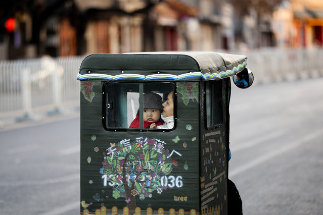 A woman and a toddler ride a tricycle taxi on a street in Beijing, Thursday, December 1, 2016. China's decision to change its one child policy and allow all married couples to have two children is expected to contribute to the country's long term economic growth and provide future relief for its greying population. (Photo by Andy Wong/AP Photo)