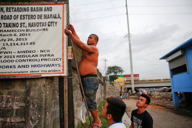 Local residents fix the street light that was broken near the C-3 bridge in North Bay Boulevard South (NBBS), a Navotas City district of slums and waterways with a high number of drug war deaths, in Manila, Philippines November 3, 2016. (Photo by Damir Sagolj/Reuters)