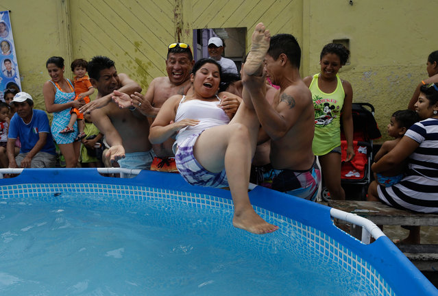 A group of friends toss Maria Carrasco into a plastic pool filled with water in Callao, Peru, Sunday, February 22, 2015. Temperatures in Callao can top 30 degrees Celsius (86 Fahrenheit) in February, which is also the month of Peru's water carnival when people celebrate with water fights and hurling water balloons. (Photo by Martin Mejia/AP Photo)