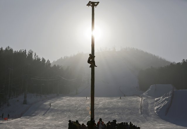A man climbs up a 13-metre-high wooden pole to to get a prize during Maslenitsa celebrations at the Bobrovy Log ski resort in the suburbs of Krasnoyarsk February 22, 2015. (Photo by Ilya Naymushin/Reuters)