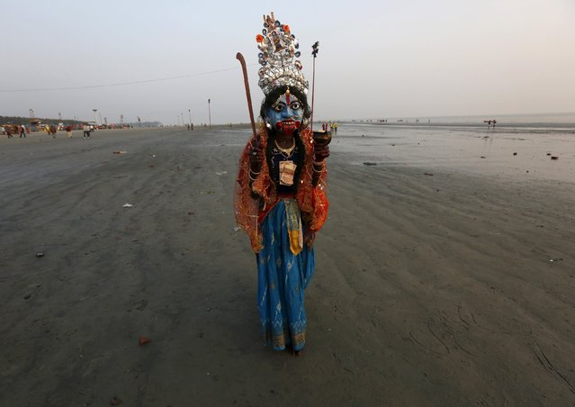 "A man dressed as Hindu goddess Kali, the goddess of power, walks for alms from Hindu pilgrims at the confluence of the river Ganges and the Bay of Bengal ahead of the ""Makar Sankranti"" festival at Sagar Island, south of Kolkata, India, January 12, 2016. (Photo by Rupak De Chowdhuri/Reuters)"