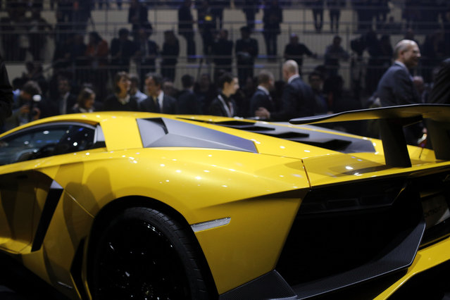 People gather around the new Lamborghini Aventador SV during a preview show of Volkswagen Group, as part of the 85th Geneva International Motor Show, Switzerland, Monday, March 2, 2015. (AP Photo/Laurent Cipriani)