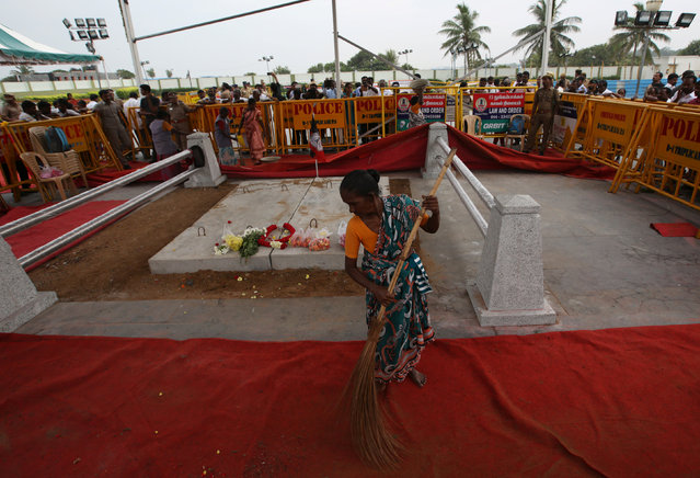A woman cleans the floor at the burial site of Tamil Nadu Chief Minister Jayalalithaa Jayaraman in Chennai, India December 7, 2016. (Photo by Adnan Abidi/Reuters)