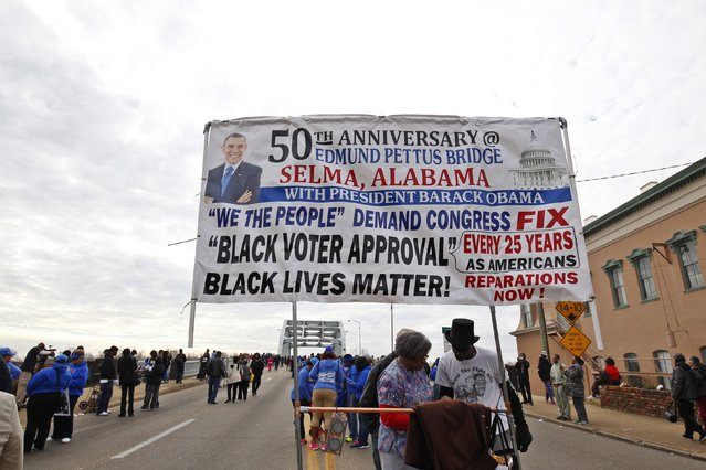 People walk along the Edmund Pettus Bridge before the beginning of the 50th anniversary of the Selma to Montgomery civil rights march in Selma, Alabama March 8, 2015. REUTERS/Tami Chappell  (UNITED STATES - Tags: POLITICS ANNIVERSARY SOCIETY)