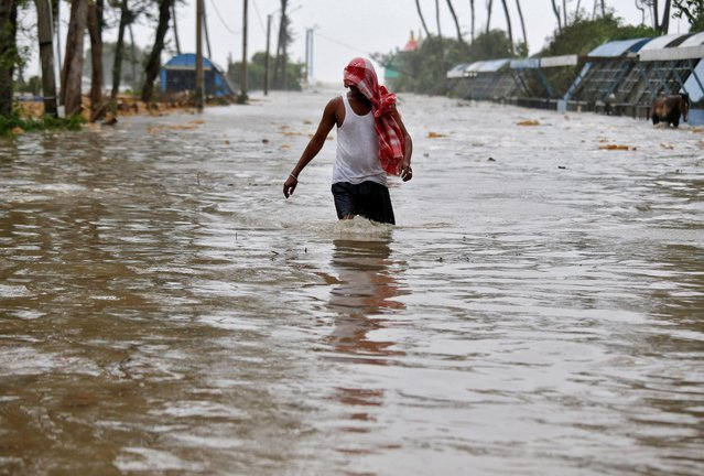 A man wades through a water-logged road after rains ahead of Cyclone Yaas at Digha in Purba Medinipur district in the eastern state of West Bengal, India, May 26, 2021. (Photo by Rupak De Chowdhuri/Reuters)