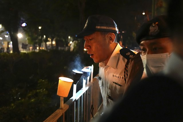 Police officers blow out candles lit by people marking the anniversary of the military crackdown on a pro-democracy student movement in Beijing, outside Victoria Park in Hong Kong, Friday, June 4, 2021. A member of the committee that organizes Hong Kong's annual candlelight vigil for the victims of the Tiananmen Square crackdown was arrested early Friday on the 32nd anniversary. (Photo by Kin Cheung/AP Photo)