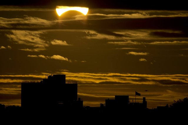A partial Solar eclipse is seen just after sunrise over the Queens borough of New York across the East River on November 3, 2013 in New York. (Photo by Stan Honda/AFP Photo)