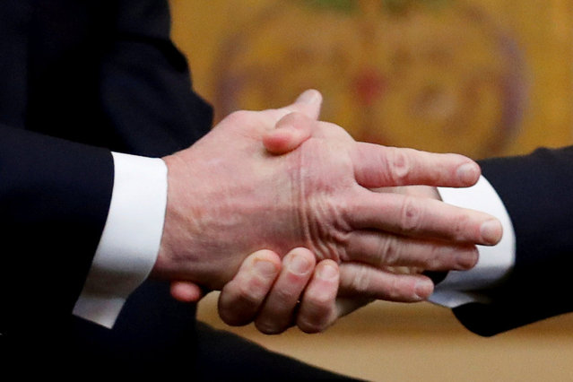 U.S. President Donald Trump shakes hands with French President Emmanuel Macron as they meet at Elysee presidential palace, as part of the commemoration ceremony for Armistice Day, 100 years after the end of the First World War, in Paris, France, November 10, 2018. (Photo by Carlos Barria/Reuters)