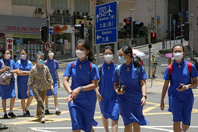 Students wearing face masks to prevent the spread of the coronavirus, walk across a street in Hong Kong, Thursday, June 10, 2021. Government officials said Thursday that they will expand the vaccination drive to about 240,000 children from 12 to 15 years old starting Friday, joining other countries such as Singapore and the U.S. that have started vaccinating children. (Photo by Kin Cheung/AP Photo)