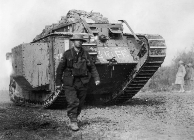 An American soldier walks ahead of an MKIV British-made tank, circa 1918. (Photo by Hulton Archive/Getty Images)