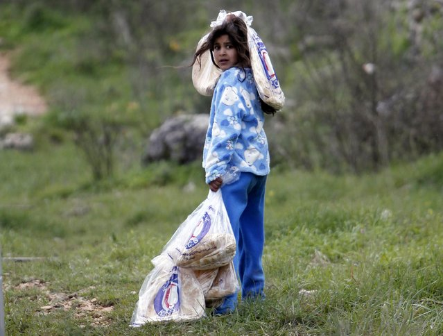 A Syrian refugee girl carries bags of bread at a makeshift settlement in the village of Ketermaya, south of Beirut January 8, 2015. (Photo by Ali Hashisho/Reuters)