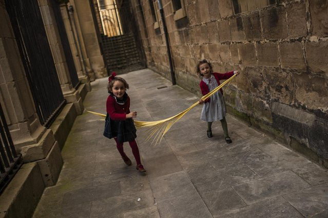 Two young girls play with their palm as they take part in a procession during Palm Sunday, a few days prior to Holy Week, in Pamplona northern Spain, Sunday, March 29, 2015. (Photo by Alvaro Barrientos/AP Photo)