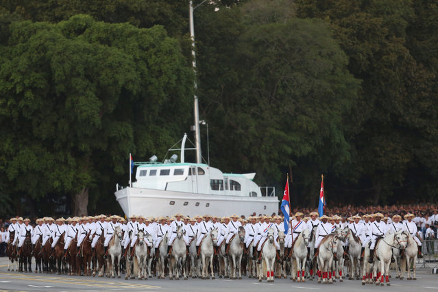"Soldiers on horseback march in front of a replica of the Granma yacht to mark the Armed Forces Day and commemorate the landing of the Granma, which brought the Castro brothers, Ernesto ""Che"" Guevara and others from Mexico to Cuba to start the revolution in 1959, in Havana, Cuba, January 2, 2017. (Photo by Alexandre Meneghini/Reuters)"
