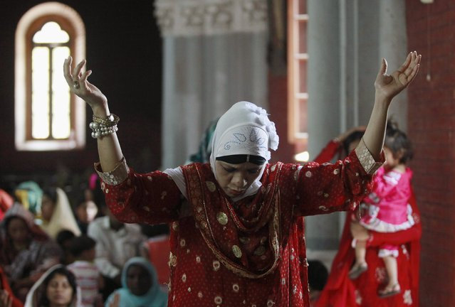 A Pakistani Christian woman prays along with others during Easter celebrations at the Sacred Heart of Jesus Church in Lahore April 5, 2015. (Photo by Mohsin Raza/Reuters)