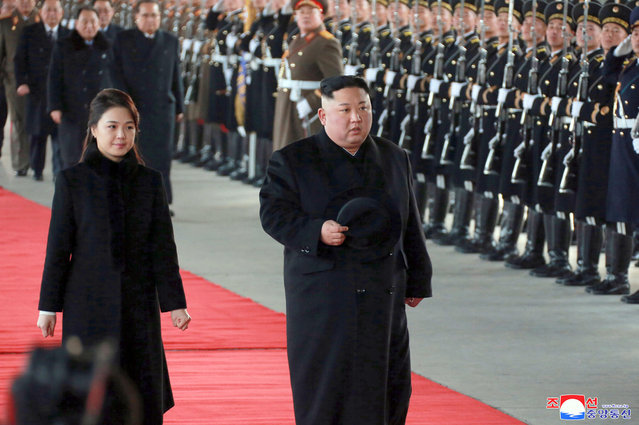 """In this Monday, Jan. 7, 2019, photo provided on Tuesday, January 8, 2019 by the North Korean government, North Korean leader Kim Jong Un walks with his wife Ri Sol Ju at Pyongyang Station in Pyongyang, North Korea, before leaving for China. Kim left for China for a four-day trip, the North's state media reported Tuesday, amid speculation that he may attempt to coordinate his positions with Beijing ahead of his likely summit with U.S. President Donald Trump. Independent journalists were not given access to cover the event depicted in this image distributed by the North Korean government. The content of this image is as provided and cannot be independently verified. Korean language watermark on image as provided by source reads: """"KCNA"""" which is the abbreviation for Korean Central News Agency. (Photo by Korean Central News Agency/Korea News Service via AP Photo)"""
