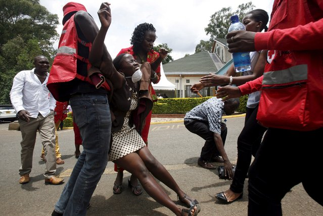 A relative is assisted by Kenya Red Cross staff as she reacts where bodies of the students killed in Thursday's attack by gunmen are preserved at the Chiromo Mortuary in the capital Nairobi April 5, 2015. The son of a Kenyan government official was one of the masked gunmen who killed nearly 150 people at a university last week, the interior ministry said on Sunday, as Kenyan churches hired armed guards to protect their Easter congregations. (Photo by Gregory Olando/Reuters)