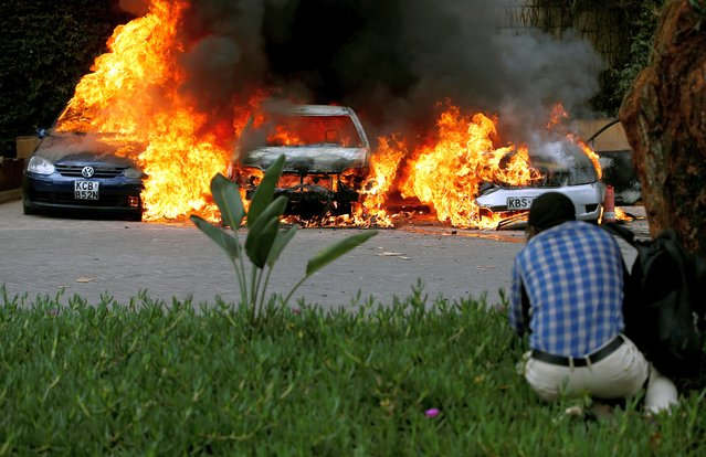 Cars are seen on fire at the scene of explosions and gunshots in Nairobi, Kenya January 15, 2019. (Photo by Thomas Mukoya/Reuters)