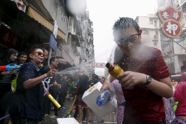A reveller reacts as he gets sprayed by water guns during Songkran Festival celebrations at Kowloon City district, known as Little Thailand as there is large number of restaurants and shops run by Thais, in Hong Kong April 12, 2015. (Photo by Tyrone Siu/Reuters)