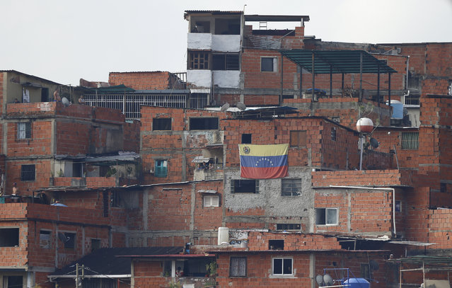 A Venezuelan flag hangs from a home in the Cotiza neighborhood where anti-government protesters clash with security forces after an apparent mutiny by a national guard unit in Caracas, Venezuela, Monday, January 21, 2019. (Photo by Fernando Llano/AP Photo)
