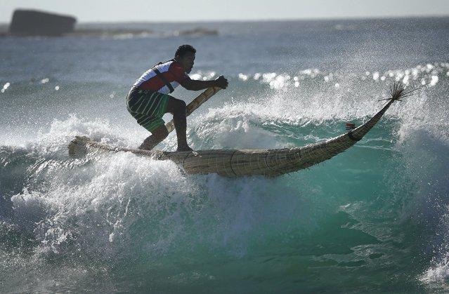 "Peruvian surfer Carlos ""Huevito"" Areola rides a reed board, or ""caballito"" (little horse), at Sydney's Bondi Beach, February 24, 2016. (Photo by Jason Reed/Reuters)"