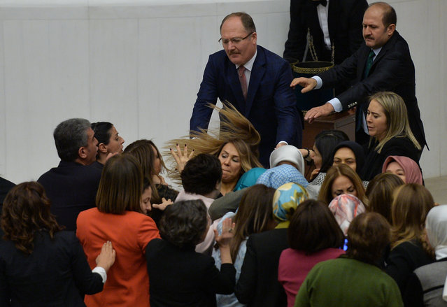 Ruling AK Party and opposition lawmakers scuffle after the independent lawmaker Aylin Nazliaka (not pictured) handcuffed herself to the rostrum during a debate to protest against the proposed constitutional changes at the Turkish Parliament in Ankara, Turkey, January 19, 2017. (Photo by Reuters/Stringer)