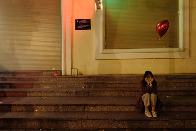 In this Saturday, February 23, 2019, photo, a woman holds a balloon near Hoan Kiem Lake in Hanoi, Vietnam. As Vietnam's capital gears up for the second summit between U.S. President Donald Trump and North Korean leader Kim Jong Un, people take time to relax at nighttime by Hoan Kiem Lake in downtown Hanoi. (Photo by Vincent Yu/AP Photo)