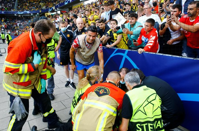 Manchester United's Cristiano Ronaldo checks on a steward after she was hit by a ball during the warm up before their Champions League match against BSC Young Boys in Bern, Switzerland on eptember 14, 2021. (Photo by Arnd Wiegmann/Reuters)