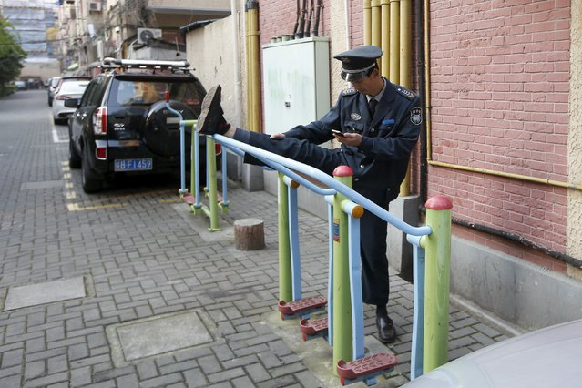 A security guard checks his phone as he exercises in Shanghai April 14, 2015. (Photo by Aly Song/Reuters)