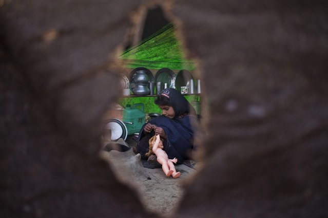A Bakarwal nomad girl, plays with her doll inside a temporary shelter on the outskirts of Srinagar, Indian controlled Kashmir, Tuesday, April 21, 2015. Bakarwals are nomadic herders of Jammu Kashmir state who wander in search of good pastures for their cattle. (Photo by Dar Yasin/AP Photo)