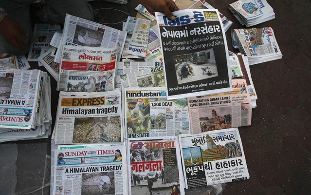 An Indian vendor displays newspapers with front-page news of Nepal earthquake for sale on a pavement in Mumbai, India, Sunday, April 26, 2015. (Photo by Rafiq Maqbool/AP Photo)