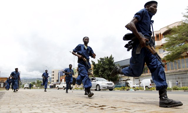 Riot policemen run as they patrol the streets during protests against the decision made by Burundi's ruling National Council for the Defence of Democracy-Forces for the Defence of Democracy (CNDD-FDD) party to allow President Pierre Nkurunziza to run for a third five-year term in office, in the capital Bujumbura, April 26, 2015. (Photo by Thomas Mukoya/Reuters)